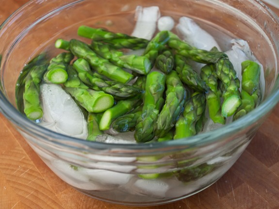 The best way to preserve the bright green color of the tips and keep them crisp is to shock them in an ice bath, but this is probably only worth it if you're entertaining. Otherwise, just refresh the tips under cold water.