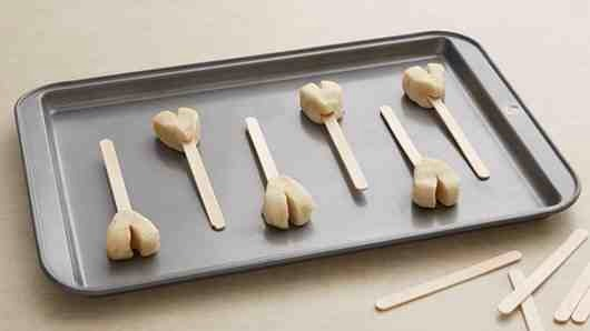 2 of 4 Place on ungreased cookie sheet 2 inches apart; insert wooden stick into bottom of each, overlapping sticks as necessary.