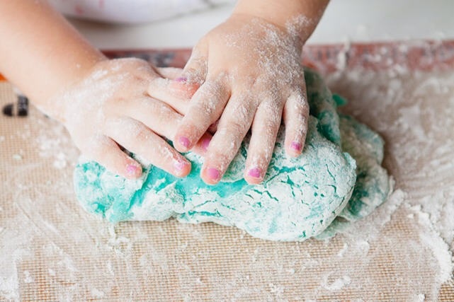 Once it is cool (at least 20-30 minutes) let the little ones knead it, adding in flour until it is no longer sticky (about 1/2 cup).  At this point, you can add in extra food coloring to make the colors more vibrant, or even add glitter.