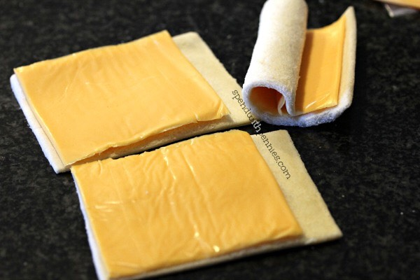 1. Using a rolling pin, roll slices of bread flat.  2. Place one slice of cheese (or 2-3 tablespoons grated cheddar). Roll up bread & cheese. Wrap one slice of bacon around each roll securing with a toothpick.