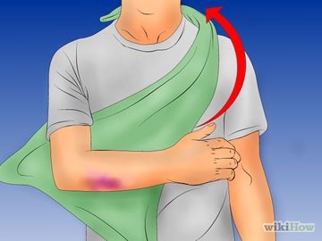 4⃣Drape one corner of the cloth over the shoulder on the uninjured side of the person, underneath the arm. The tip of the triangle should be facing away from the person's body and the largest portion of the triangle should be close to the person's arm.