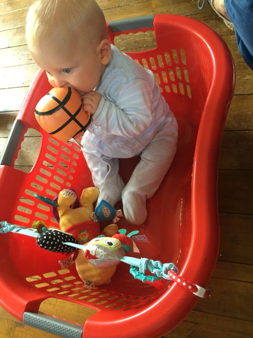 For babies just learning to sit without toppling over a wash basket makes a great play pen!