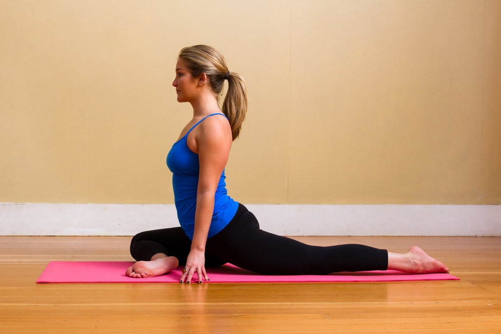 Pigeon pose: go on all fours and bring your right knee forward between your hands so it's resting on the bed. Make sure your left leg is in line with its own hip socket and your left foot is laying flat. Fold forward over your right knee. This pose is an intense leg stretch that will energize you.