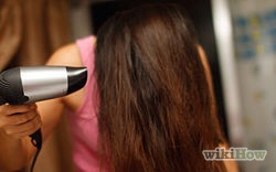 Once hair is damp, take a round brush and blow dry your hair straight down with a diffuser (this will straighten hair).