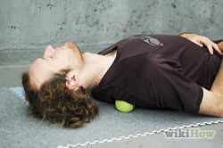 Place a tennis ball right beneath your knot and lie directly on it. You should feel some pressure as your body weight is placed on the ball.
