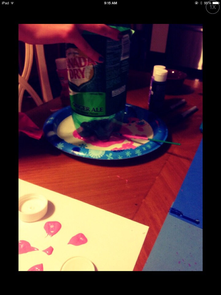 Once you're done coloring in your tree, squeeze some pink paint onto a paper plate and dip your soda bottle into it.