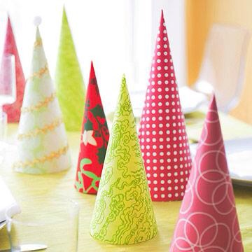 """Row of paper trees  Turn holiday-theme scrapbooking papers into an inexpensive tabletop display. Cut and fold papers to create simple cone """"trees"""" of different sizes. Secure seams with double-sided tape."""
